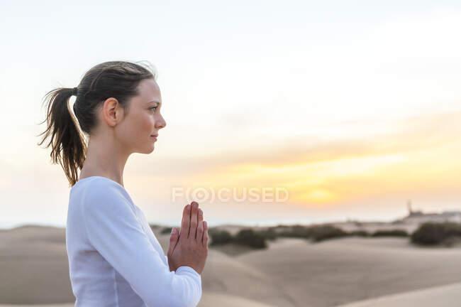 Женщина медитирует на закате в дюнах, Гран-Канария, Испания — стоковое фото