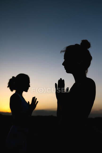Жінки в молитовному положенні стоять надворі під час заходу сонця. — стокове фото