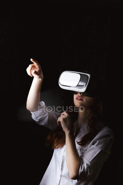 Mujer joven haciendo gestos mientras usa gafas VR sobre fondo negro - foto de stock