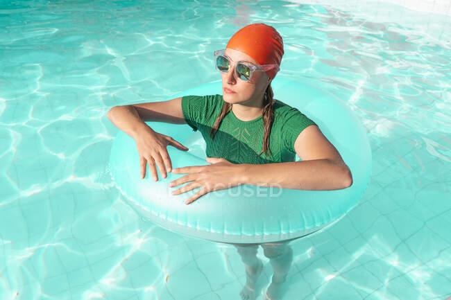 Retrato de mujer con neumático flotante de pie en la piscina - foto de stock