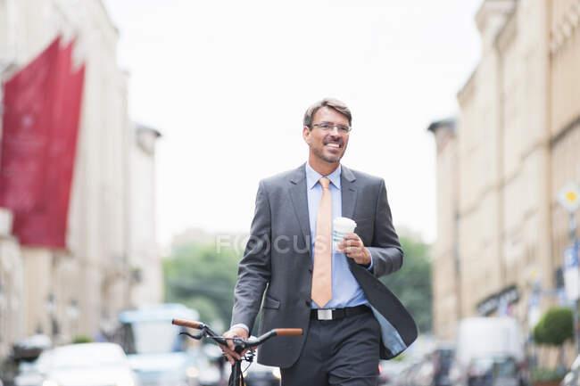 Homme d'affaires souriant tenant le café regardant loin tout en marchant à vélo en ville — Photo de stock
