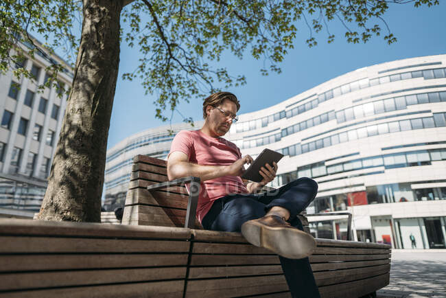 Freelancer sitting on a bench in the city using tablet — Stock Photo