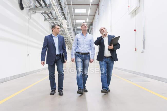 Троє бізнесменів ходять і розмовляють по коридору. — стокове фото