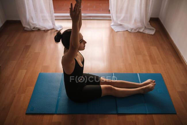 Молодая женщина с поднятыми руками занимается спортом, сидя дома на коврике — стоковое фото