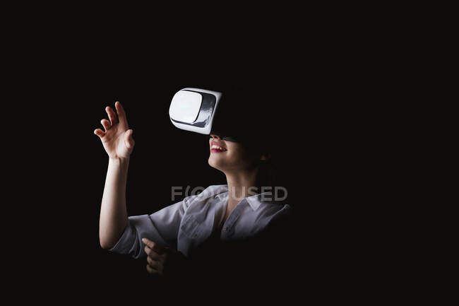 Young woman using VR glasses against black background — Stock Photo