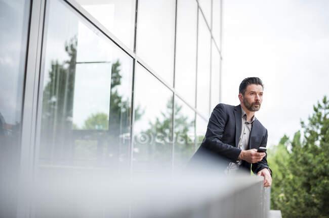 Духовний бізнесмен, який спирається на поручні, дивлячись з офісного балкона — стокове фото
