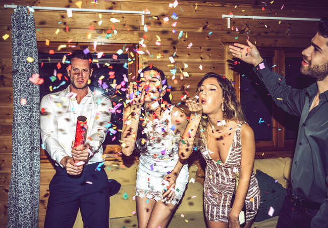 Felice maschio e femmina amici che giocano con coriandoli in festa. — Foto stock