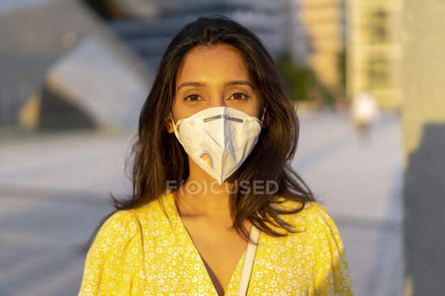 Mujer joven y segura con máscara facial en la ciudad - foto de stock