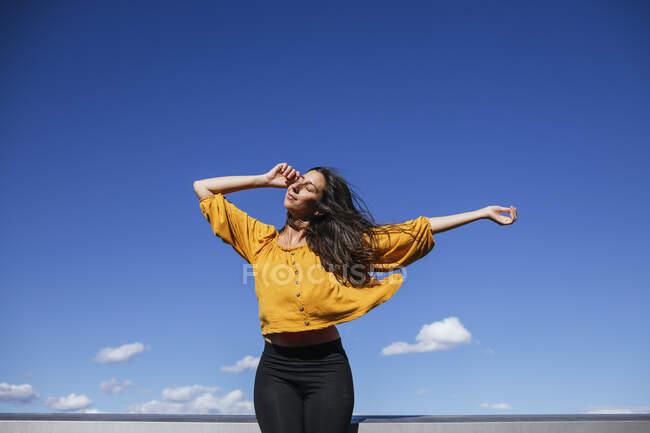 Mulher despreocupada dançando no terraço do telhado à luz do sol — Fotografia de Stock