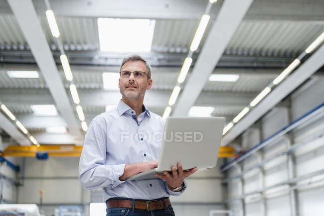 Доросла людина тримає ноутбук на підлозі фабрики. — стокове фото