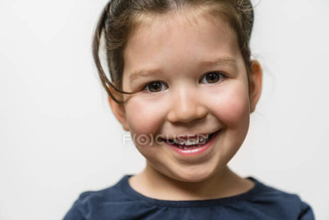 Portrait of happy girl against white background — Stock Photo
