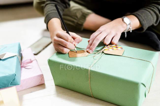 Женские руки пишут на теге — стоковое фото