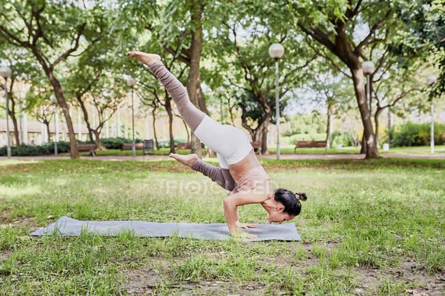 Взрослая женщина практикующая йогу на коврике в парке, поза ворона — стоковое фото