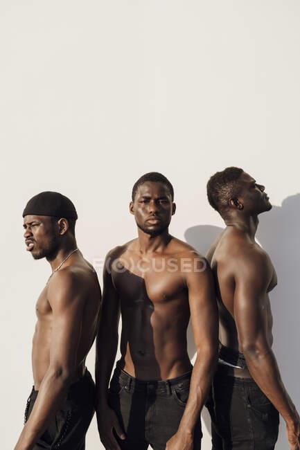 Tres hombres negros con el pecho desnudo de pie delante de la pared blanca - foto de stock