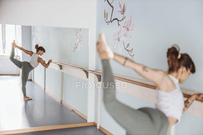 Отражение балерины, делающей упражнения на растяжку в зеркале в танцевальной студии — стоковое фото