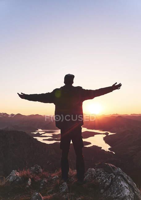 Молодий чоловік - турист стоїть з витягнутими руками на горі під час заходу сонця (Леон, Іспанія). — стокове фото