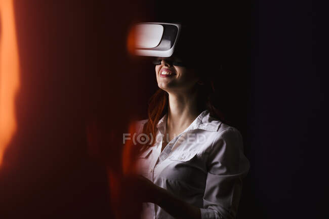 Young woman smiling while using VR glasses over black background — Stock Photo