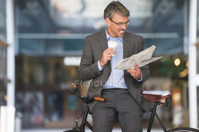 Homme d'affaires souriant tenant le journal de lecture de café tout en étant assis sur le vélo — Photo de stock