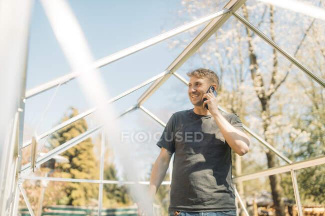 Hombre hablando por teléfono inteligente mientras está de pie en el invernadero incompleto en el patio - foto de stock