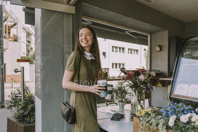 Улыбающаяся женщина с опущенной маской для лица, держащая два кофе на вынос — стоковое фото