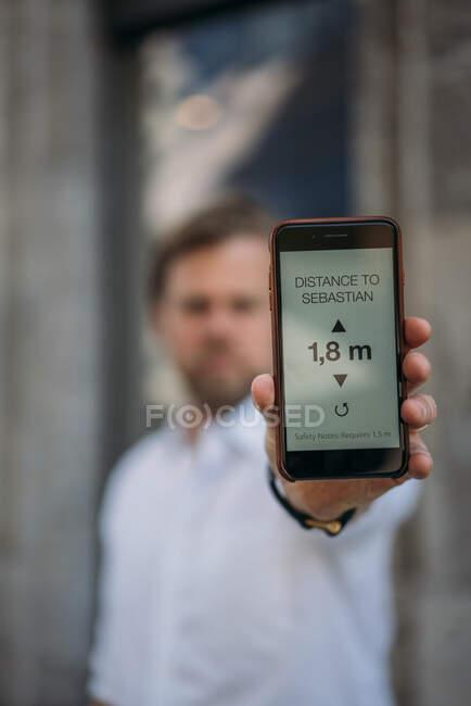 Close-up de homem segurando smartphone mostrando distância na tela — Fotografia de Stock