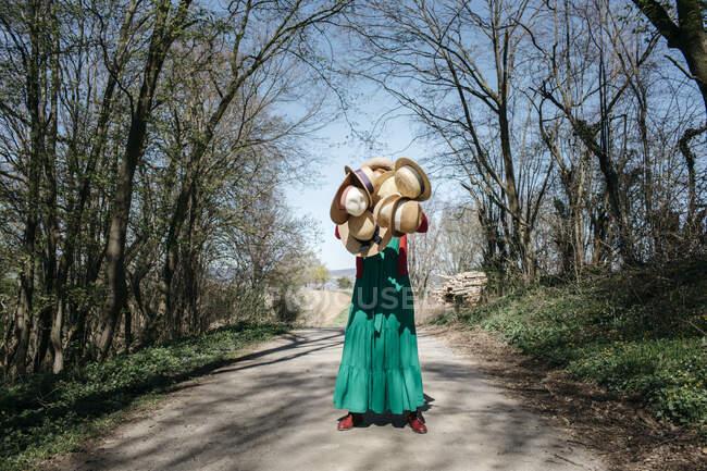 Mulher escondida atrás de muitos chapéus de palha — Fotografia de Stock