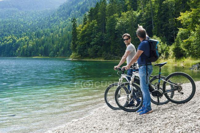 Homem sênior e maduro com e-bikes em Eibsee à beira do lago — Fotografia de Stock