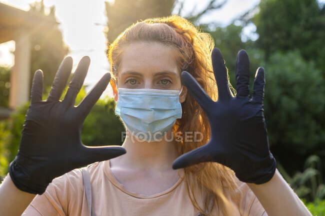 Зблизька молода жінка в масці і рукавичках з руками на подвір'ї — Stock Photo