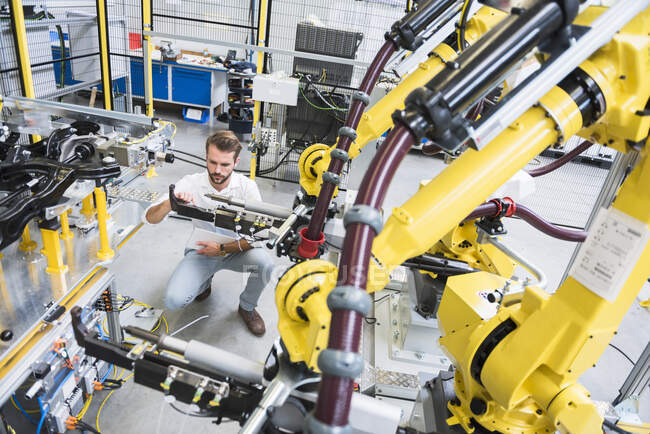 Full length of young engineer crouching while examining computer-aided machinery in automated industry — Stock Photo