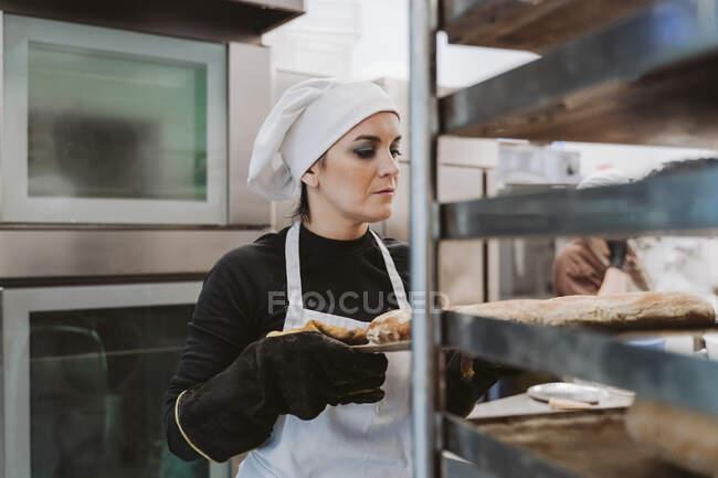 Жіночий пекар тримає пекарню в пекарні. — стокове фото