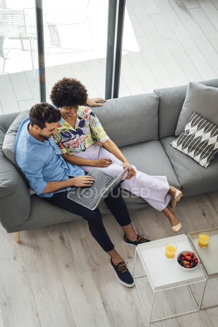 Couple multi-ethnique utilisant un ordinateur portable tout en étant assis sur le canapé dans un penthouse — Photo de stock