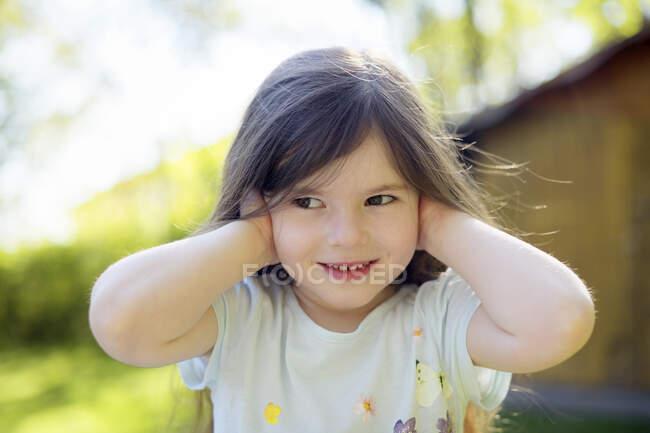 Милая девушка закрывает уши во дворе в солнечный день — стоковое фото