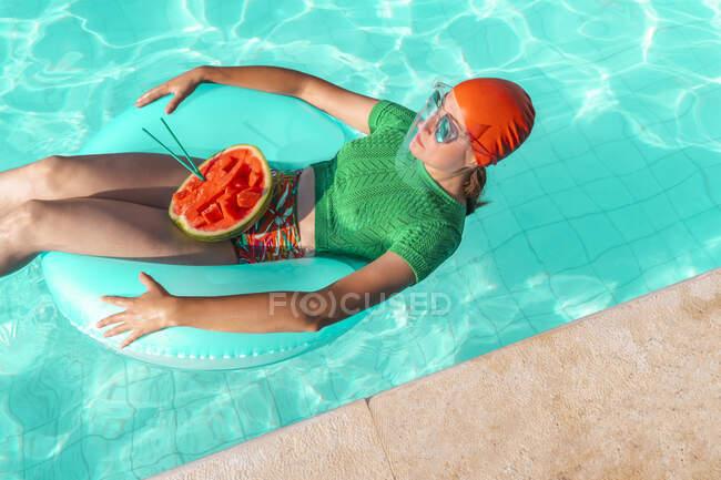 Mujer con neumático flotante y sandía en piscina - foto de stock