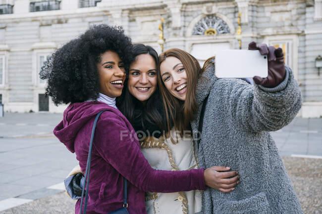 Felices amigas tomando selfie con teléfono inteligente mientras se enfrentan al Palacio Real de Madrid, España - foto de stock