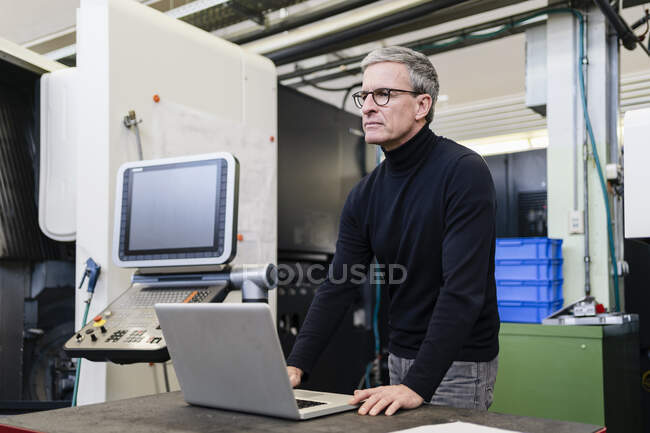 Thoughtful male supervisor standing with laptop at table in factory — Stock Photo