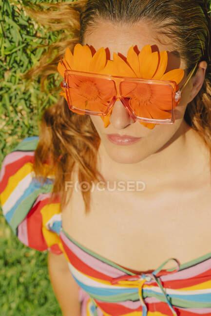 Retrato de mujer acostada en un prado con gafas con flores naranjas cubriendo sus ojos - foto de stock