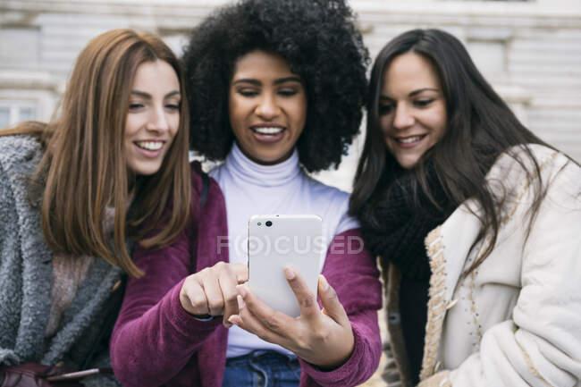 Primer plano de la mujer joven mostrando el teléfono inteligente a las amigas sentadas al aire libre - foto de stock