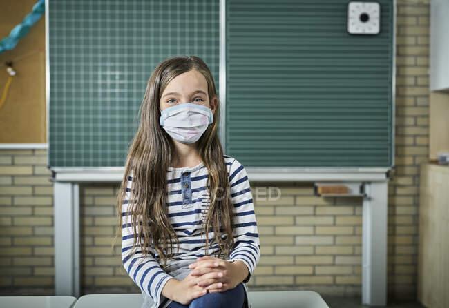 Retrato de menina usando máscara em sala de aula — Fotografia de Stock