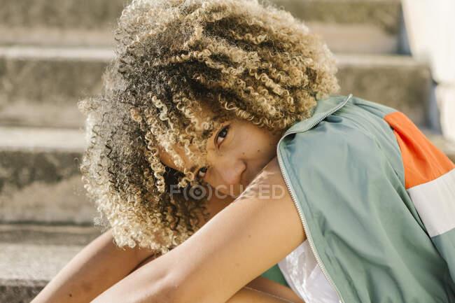 Mujer joven y segura sentada en los escalones durante el día soleado - foto de stock