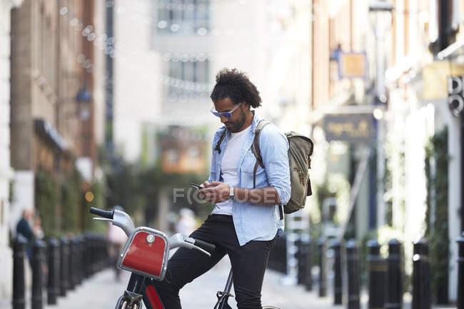 Jovem com bicicleta alugada e mochila usando telefone celular na cidade, Londres, Reino Unido — Fotografia de Stock
