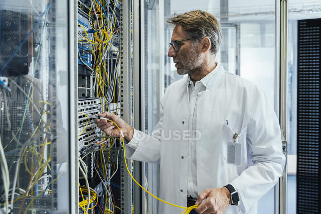 Mature man plugging transceiver on fiber optic cable into rack — Stockfoto