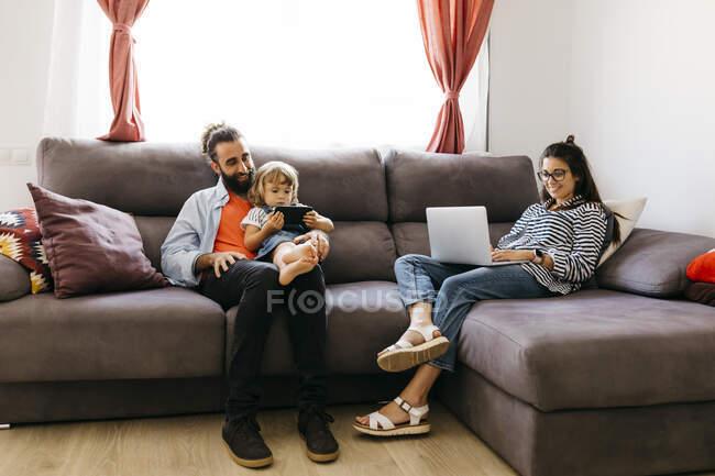 Mujer trabajando sobre el ordenador portátil, mientras que el padre y la hija utilizando el teléfono móvil en el sofá en la sala de estar - foto de stock