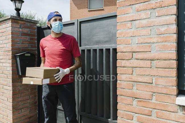 Средний взрослый мужчина курьер смотрит в сторону, держа пакет и стоя напротив ворот дома — стоковое фото