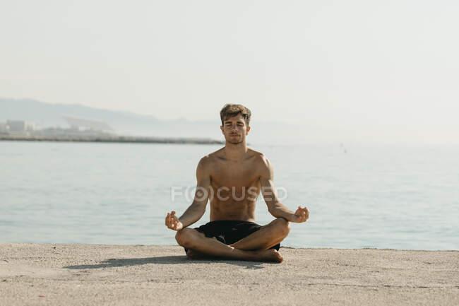 Молодой человек без рубашки медитирует, сидя у моря в гавани — стоковое фото