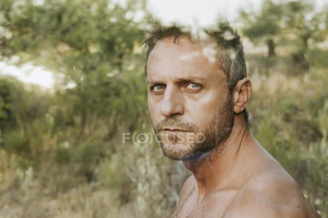 Primer plano del hombre guapo sin camisa contra los árboles en el bosque visto a través del vidrio - foto de stock
