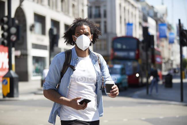 Портрет молодого чоловіка у захисній масці, що переходить дорогу, Лондон, ук. — стокове фото
