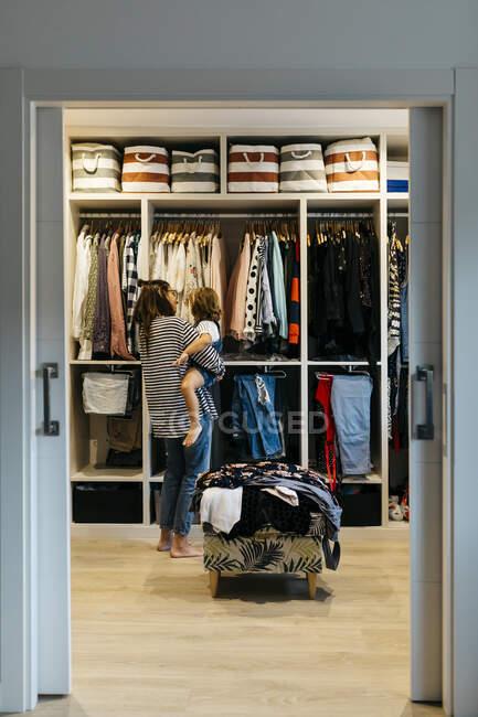 Mãe com a filha escolhendo roupas no camarim em casa visto através da porta — Fotografia de Stock