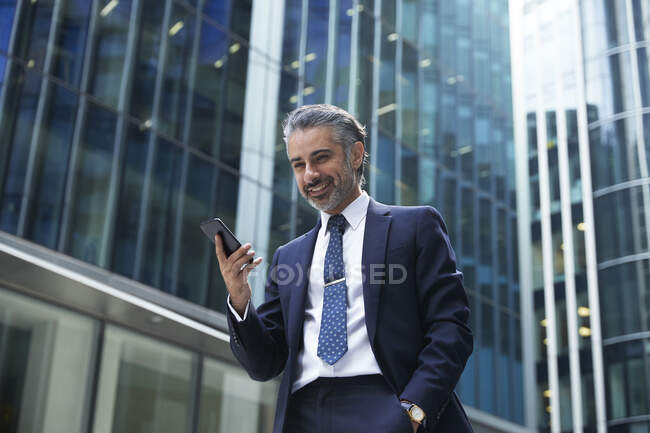 Smiling businessman using mobile phone outside office building in city — стокове фото