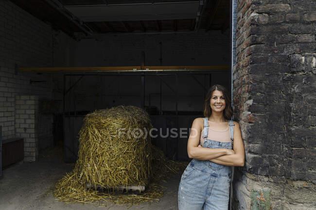 Retrato de uma jovem sorridente encostada à parede de tijolos em um celeiro em uma fazenda — Fotografia de Stock