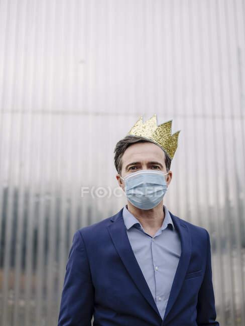 Retrato de un hombre de negocios maduro con una corona de juguete y mascarilla protectora - foto de stock